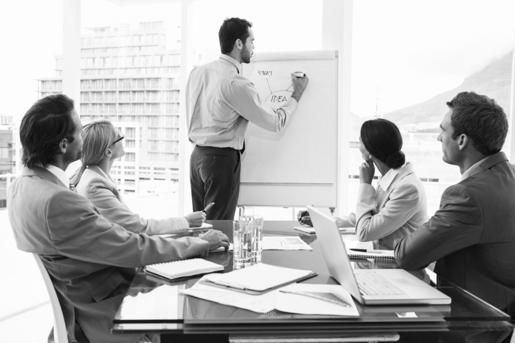 PHOTO business man giving presentation to group in conference room BW