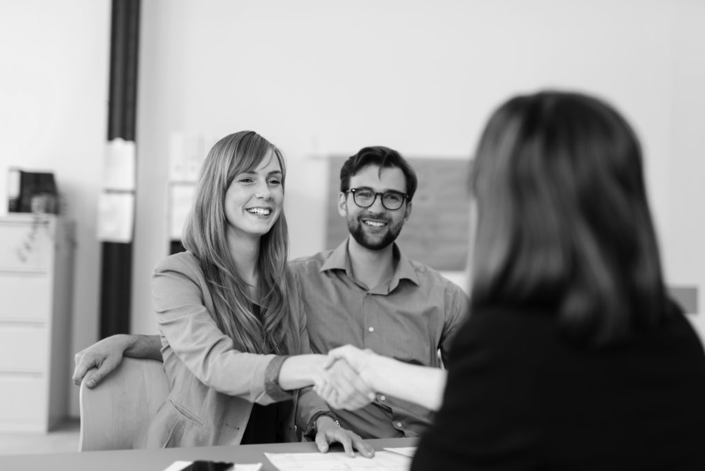 consultants in group working at desk shaking hands