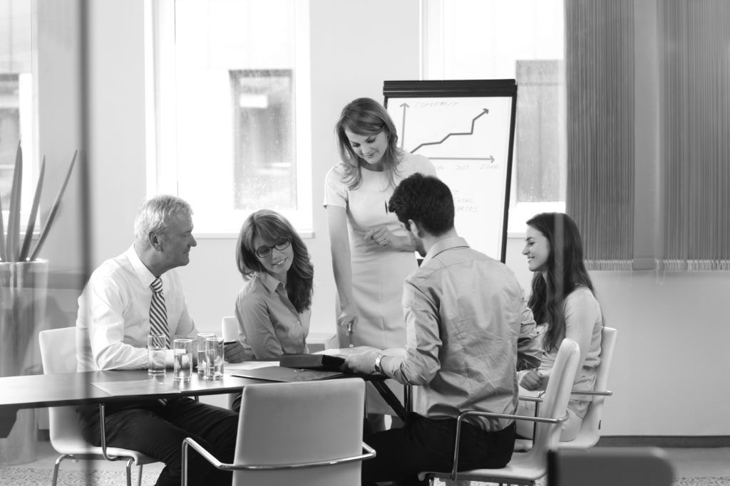 consultants in group working at desk looking at chart
