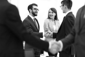 consultants working in office shaking hands