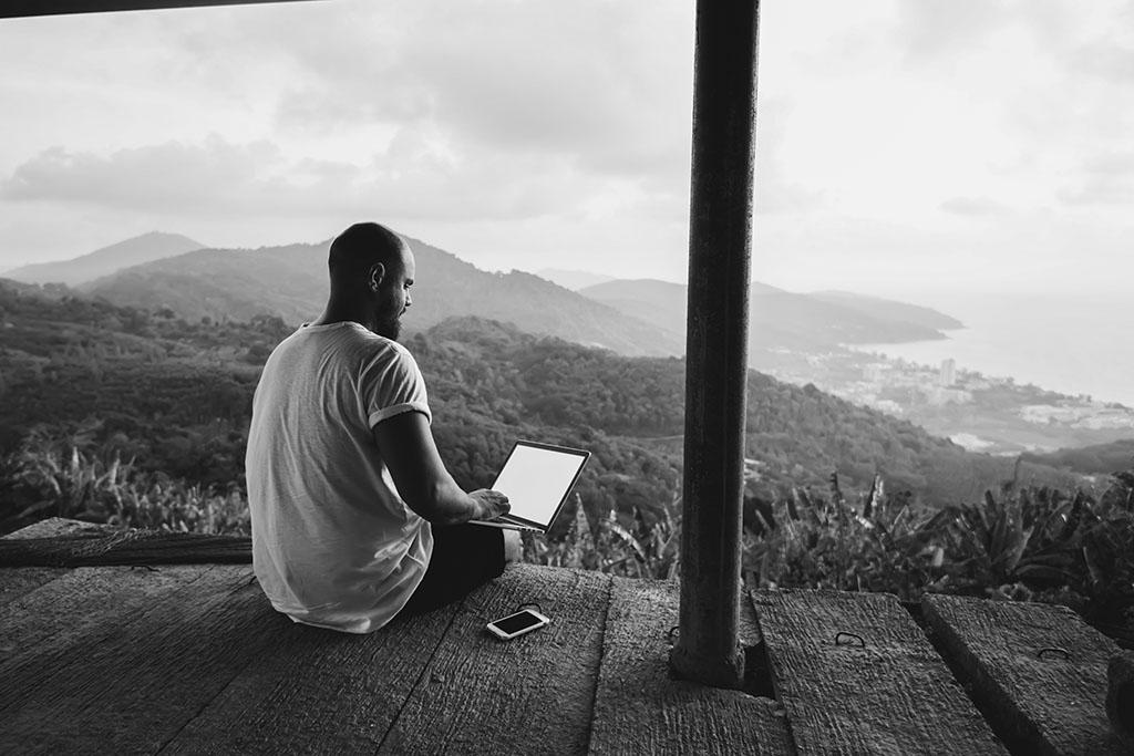 man working at computer looking at mountain