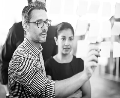 rsz_photo_man_pointing_to_sticky_notes_on_glass_wall_showing_colleagues_bw